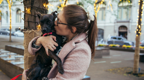 Jamie is holding Lucy in her arms, facing to her right. Her hair is in a bun and she is wearing a light pink jacket. She is kissing the side of Lucy's face. Lucy is wearing a red collar and looking at the camera.